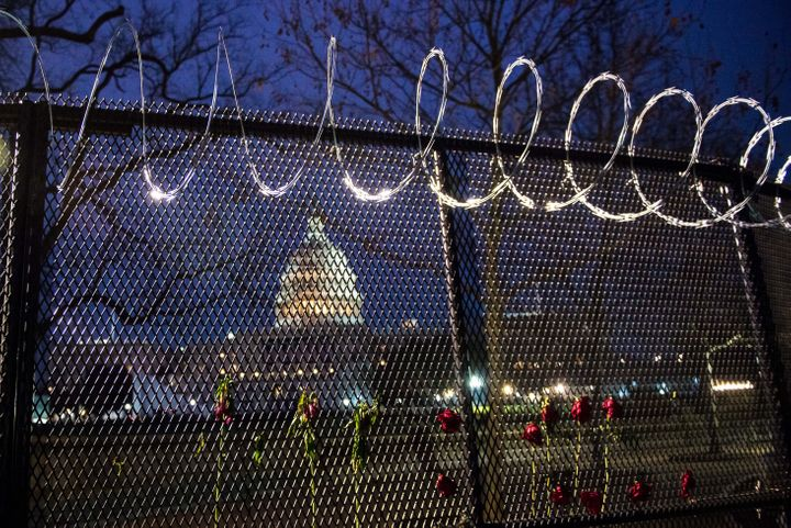 Flowers are placed along the razor wire fencing that now surrounds the U.S. Capitol on Jan. 15.