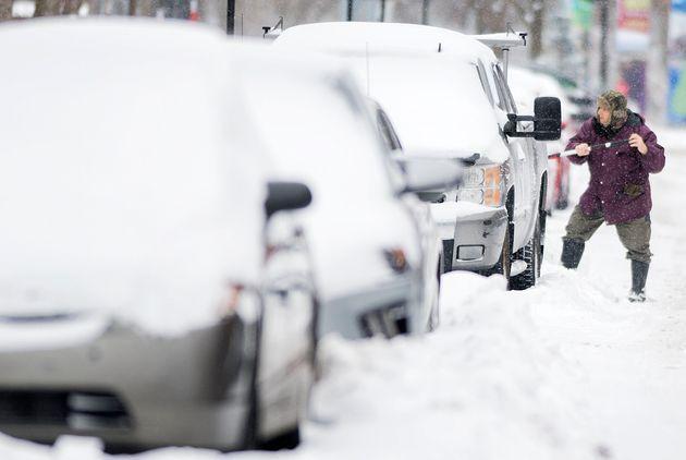 Un homme déneige sa voiture à Montréal (photo
