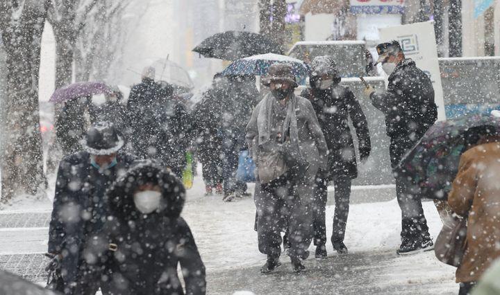폭설이 내리고 있는 12일 오후 서울 서초구 교대역 인근에서 우산을 쓴 시민들이 발걸음을 재촉하고 있다.