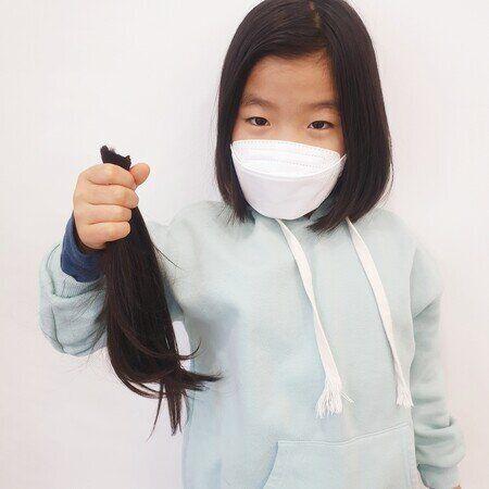 경기 양주시 남면초 2학년 장시유 양이 지난 11일 소아암을 앓는 친구들에게 보내기 위해 자른 머리카락을 들고