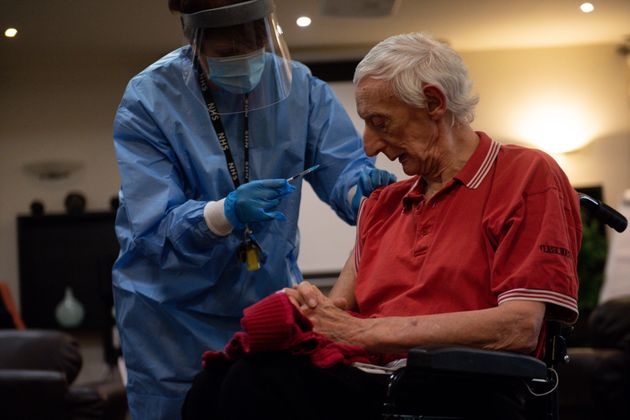 Care home resident David Price receives an injection of the coronavirus vaccine at Andrew Cohen House...