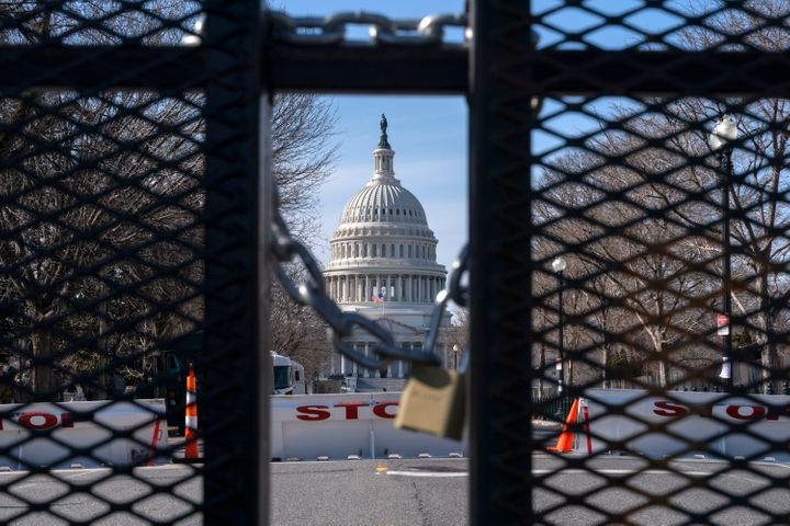 With the U.S. Capitol in the background, a lock on anti-scaling security fencing is seen on Saturday, Jan. 16, 2021, in Washi