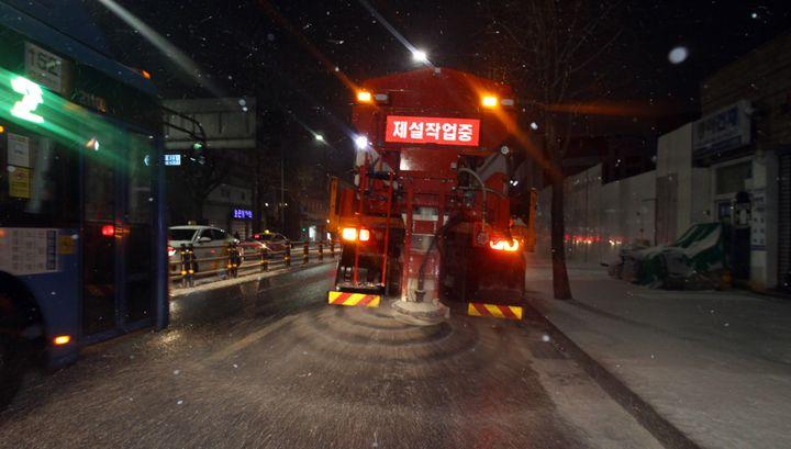 전국 곳곳에 대설 특보가 발효중인 17일 저녁 눈이 내린 서울 동작구 장승배기역 인근 상도로에서 제설 차량이 도로에 염화칼슘을 뿌리며 이동하고 있다.