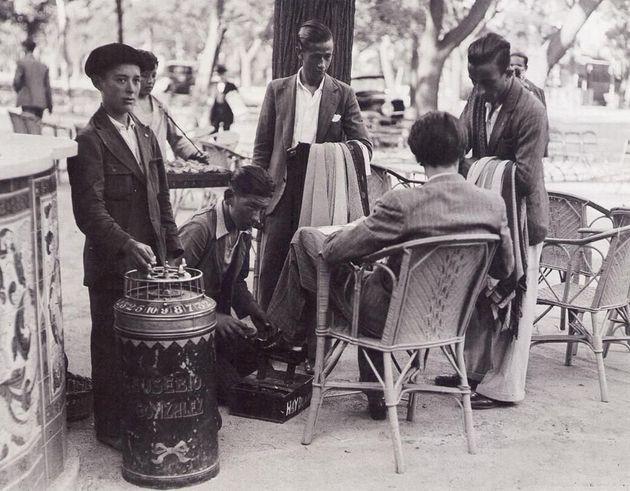 Vecino rodeado por barquillero, limpiabotas y dos vendedores ambulantes de corbatas en Madrid, hace 85