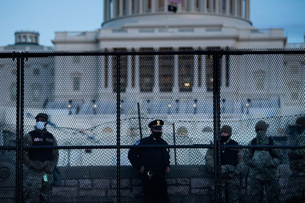 TOPSHOT - A Capitol Police officer stands with members of the National Guard behind a crowd control fence...