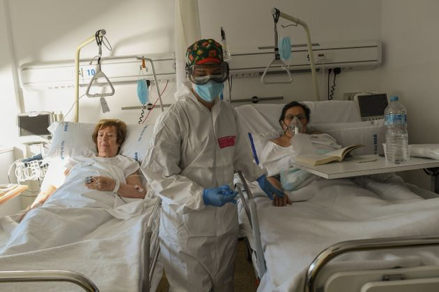 Una enfermera atiende a dos pacientes en un hospital de