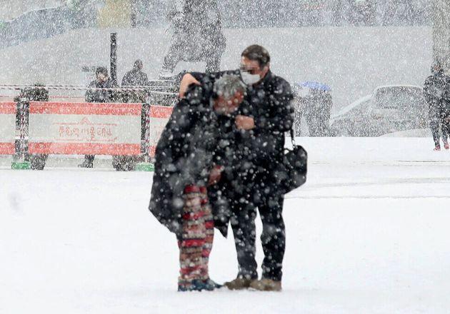갑작스럽게 많은 눈이 내린 18일 오전 서울 중구 서울역 앞에서 한 시민이 거리 노숙인에게 자신의 방한 점퍼와 장갑을 벗어주고