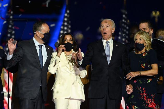 Kamala Harris, de blanco, y Joe Biden, a su derecha, celebran su victoria tras haber sido declarados...