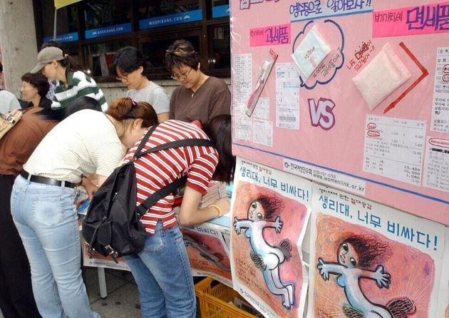 2002년 8월23일 한국여성민우회가 연 '생리대 가격, 너무 비싸지 않니?' 거리 캠페인에서 시민들이 생리대 부가가치세 폐지에 동의하는 서명을 하고 있다. 세제...