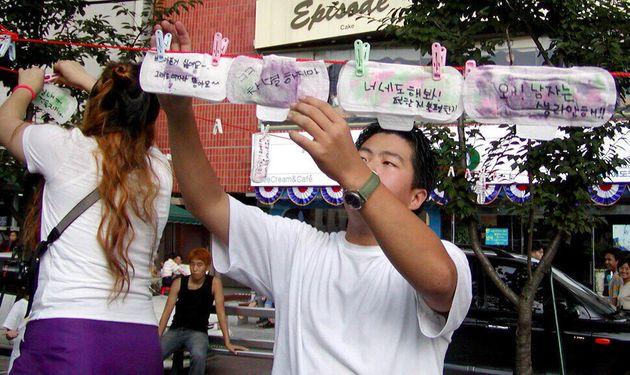 2002년 8월18일 서울 신촌에서 열린 월경페스티벌 거리홍보전에서 여성들이 월경에 대한 느낌을 쓴 생리대를 한 남성이 빨랫줄에 널고 있다. 1999년 4개 대학교 학생들의 연합 '불턱'이...