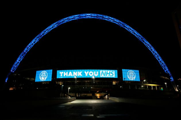 Wembley stadium is seen lit up blue for the Clap For Our Carers campaign in support of the NHS during...