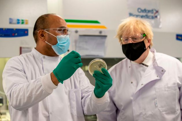 Boris Johnson speaks with Dipesh Sonar as he visits the quality control laboratory at Oxford BioMedica...