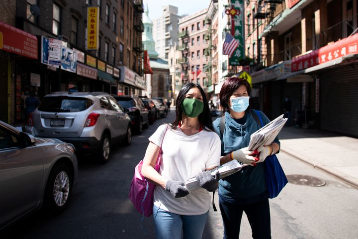 Shirley Ng (l) , a volunteer with the Chinatown Block Watch neighborhood patrol group, distributes Chinese newspaper along a