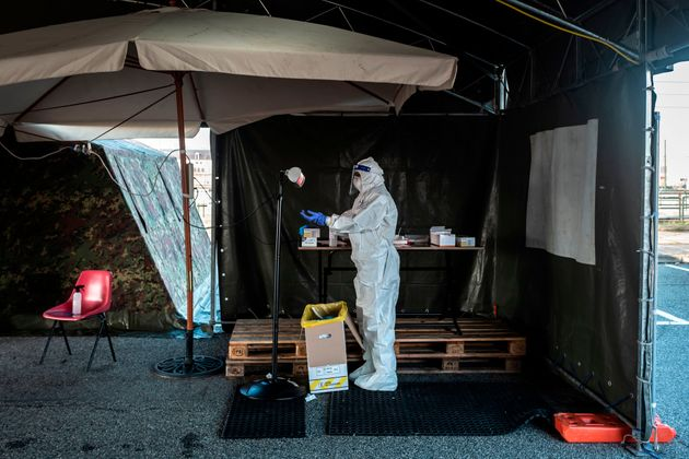 TOPSHOT - A military medical worker adjusts her gloves on January 12, 2021 prior to collect swab samples...