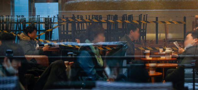포장·배달만 가능했던 카페에서 매장 내 취식이 가능해진 18일 서울시내 카페를 찾은 시민들이 테이블에