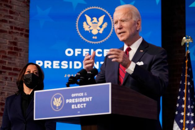 Vice President-elect Kamala Harris listens as President-elect Joe Biden speaks during an event at The...
