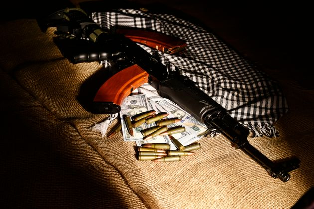 Combat weapons, US dollars and ammunition scattered on a