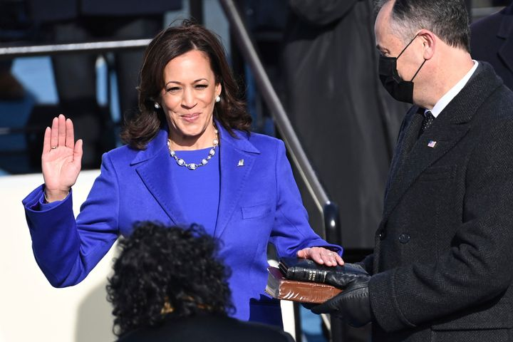 Kamala Harris — flanked by her husband, Doug Emhoff, who is holding two Bibles — is sworn in as vice president by