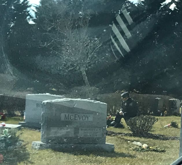 A lone man in a blue uniform kneels at the grave of Beau Biden at St. Joseph on the Brandywine church...