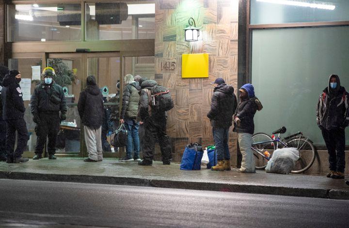 Les gens font la file devant un hôtel pour sans-abri avant 20 h, le lundi 11 janvier 2021, à Montréal.