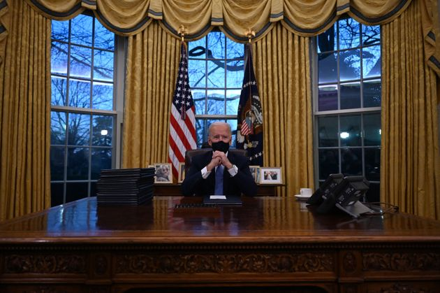 US President Joe Biden sits in the Oval Office at the White House in Washington, DC, after being sworn...