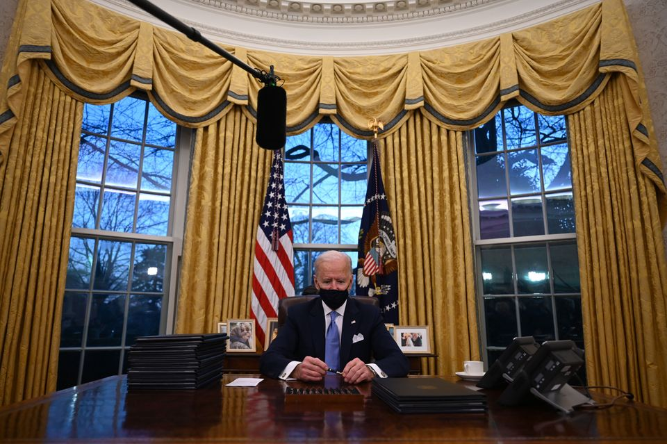 U.S. President Joe Biden holds a pen as he prepares to sign a series of orders in the Oval Office of...