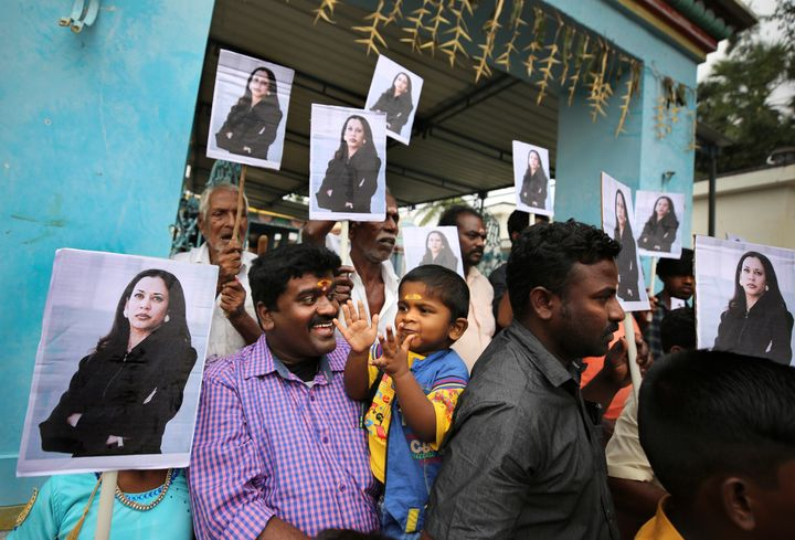 Villagers hold placards featuring U.S. Vice President Kamala Harris after participating in special prayers at a Hindu temple