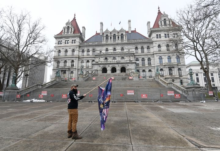 Trump supporter Mark Leggiero, of Florida, N.Y., holds a banner outside the New York state Capitol objecting to the inaugurat