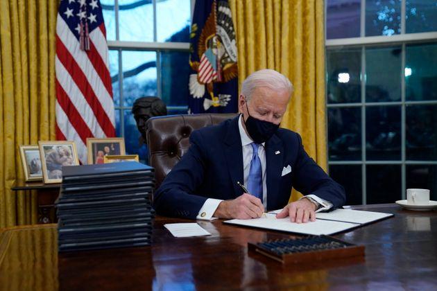 El presidente de EEUU, Joe Biden, firmando sus primeros decretos en el Despacho