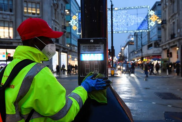 A street cleaner pictured in December sanitising the button on a pedestrian