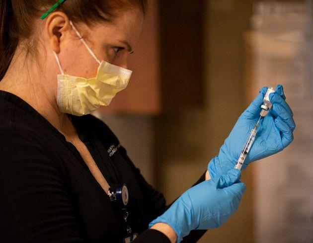 A pharmacist prepares vials of coronavirus vaccine (file