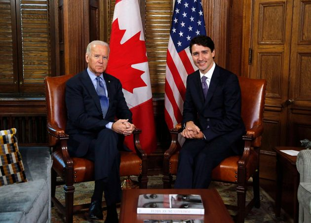 Joe Biden sits beside Prime Minister Justin Trudeau for a photo on Parliament Hill in Ottawa while he...