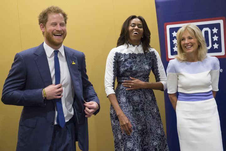 Harry, first lady Michelle Obama and Jill Biden laugh as they listen to a music presentation by wounded warriors at the USO W
