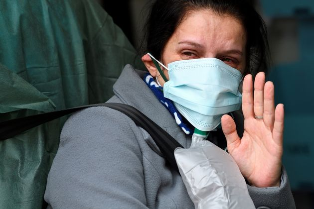 A woman possibly suffering with the coronavirus disease (COVID-19) waves goodbye to her family before...