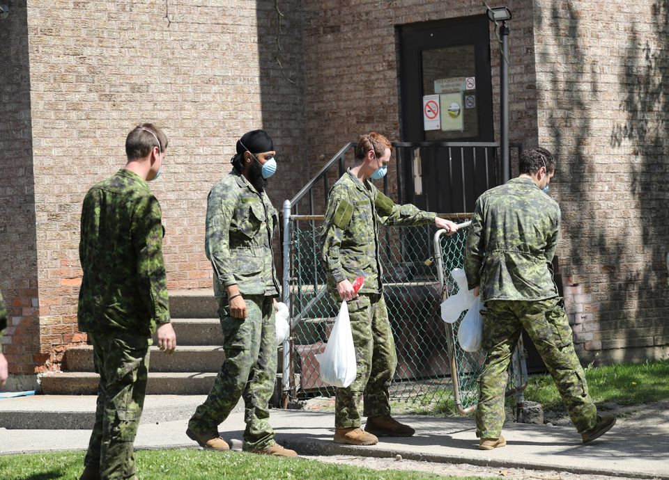 Military personnel are seen changing shifts behind the Eatonville Care Centre in Toronto on May 26,