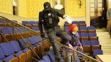 A man in camouflage swing plastic had restraints, identified by the FBI as Eric Munchel, jumps among the seats in the Senate chamber after the Capitol was stormed Jan. 6.
