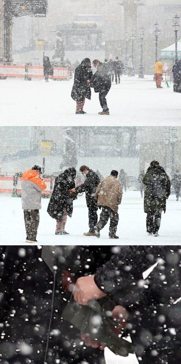 갑작스럽게 많은 눈이 내린 지난 18일 오전 서울 중구 서울역 앞에서 한 시민이 노숙인에게 자신의 방한점퍼와 장갑을 벗어 주고