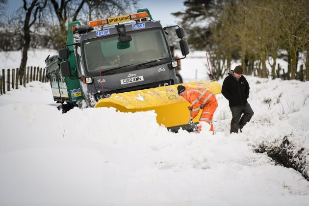 Men clear snow around a plough which had become stuck in a snow drift in Lamancha,