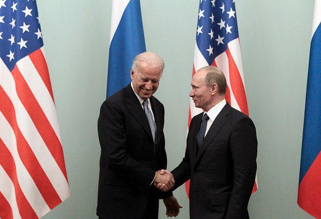 Russian Prime Minister Vladimir Putin (R) shakes hands with U.S. Vice President Joe Biden during their...