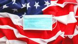 Covid-19 Coronavirus in USA. Protective surgical face mask on American national flag. U.S. flag and hygienic mask as symbol of protection prevention viral infection coronavirus. Medicine health care.