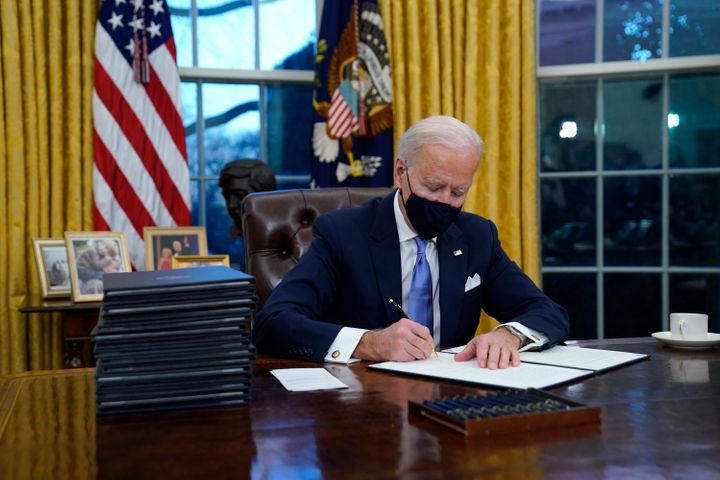 President Joe Biden signs his first executive order in the Oval Office of the White House on Wednesday, Jan. 20, 2021, in Was
