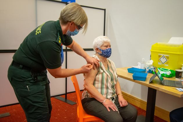 An elderly woman receives an injection of a Covid-19 vaccine at a NHS vaccination centre that has been...