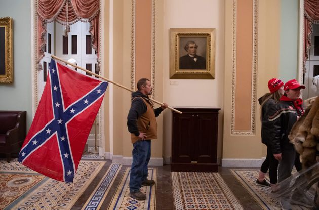 A supporter of Donald Trump holds a Confederate flag outside the Senate Chamber during a protest after...