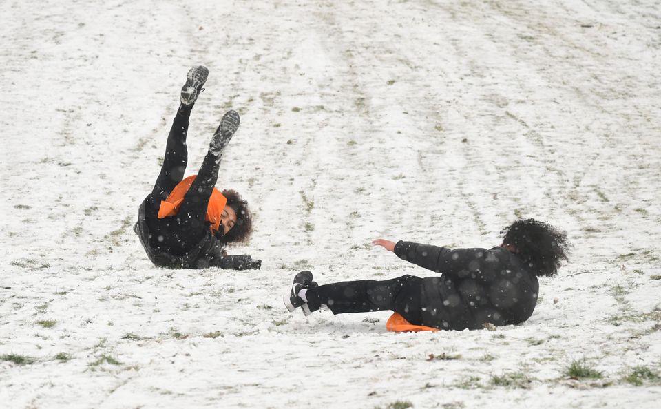 People sledging in a snowy Greenwich Park in