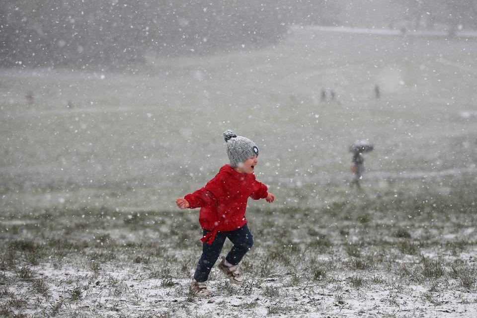 A child runs around as snow falls on Hampstead Heath in