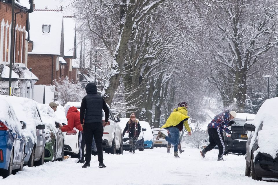 A snowball fight in the snow in Moseley, Birmingham, United