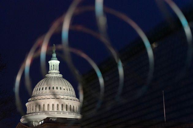 Le Capitole est visible à travers les barbelés au-dessus des clôtures, le 16 janvier...