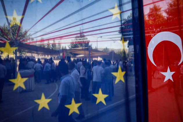 People are seen behind a European Union and a Turkish flag, as they attend an gastronomy event in Mardin,...