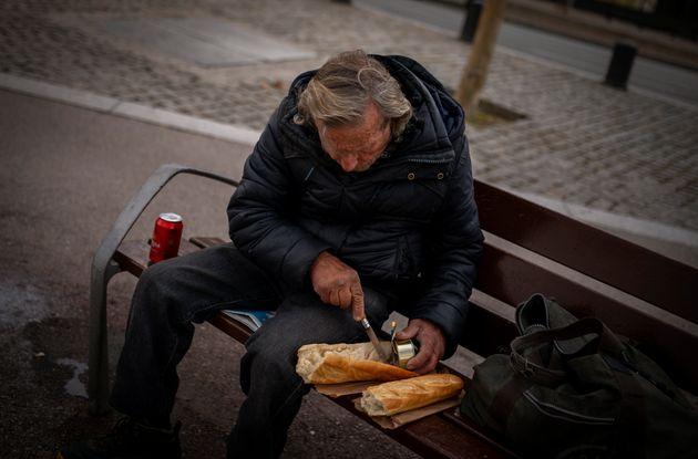 Un hombre sin hogar se prepara un bocadillo en un banco de un parque de Barcelona, el pasado 20 de