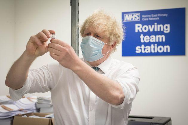 Boris Johnson, Premier ministre du Royaume-Uni, observant une dose de vaccin Oxford/AstraZeneca contre...